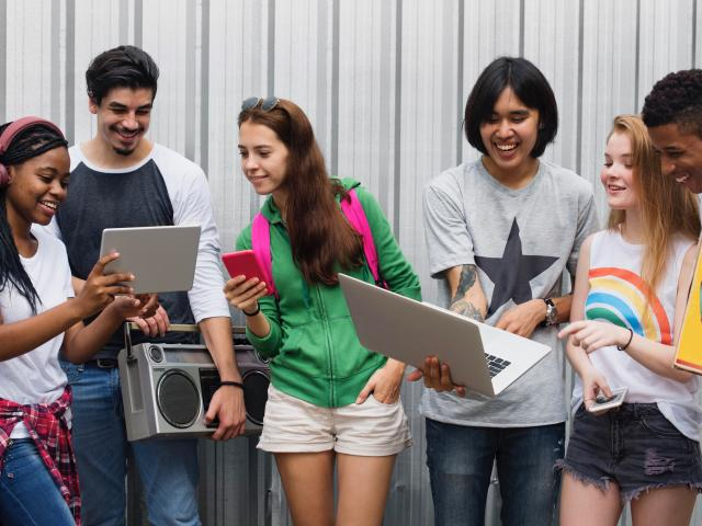 Group of teens hanging out sharing technology
