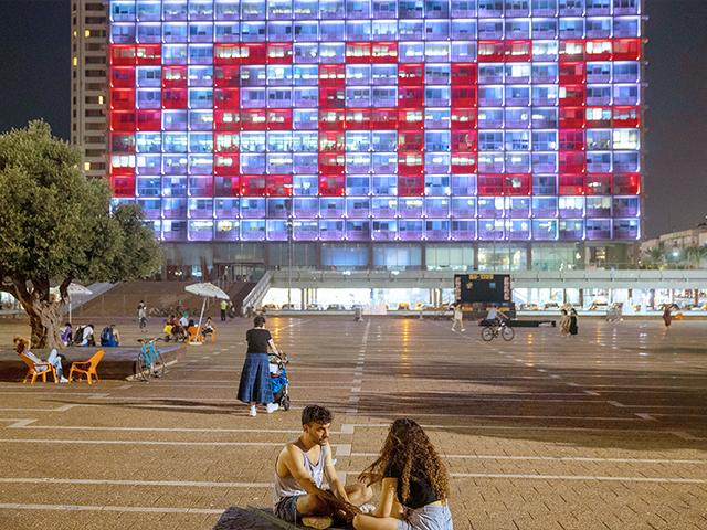 Tel Aviv City Hall is lit up with the words for peace in Hebrew, Arabic and English in honor of the recognition agreements Israel signed with the UAE and Bahrain at the White House, in Tel Aviv, Israel. (AP Photo/Oded Balilty)