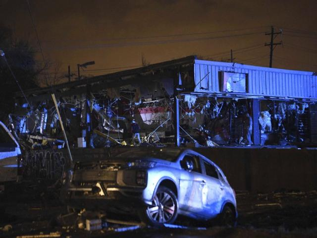 People survey the damage to a building in East Nashville after a tornado hit the city in the early morning hours of Tuesday, March 3, 2020. (Courtney Pedroza/The Tennessean via AP)