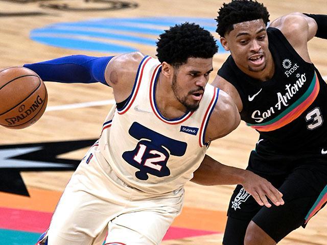 Philadelphia 76ers' Tobias Harris (12) drives around San Antonio Spurs' Keldon Johnson during the second half of an NBA basketball game on Sunday, May 2, 2021, in San Antonio. (AP Photo/Darren Abate)