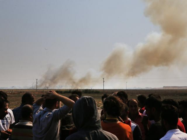 Smoke billows from fires on targets in Tel Abyad, Syria, caused by bombardment by Turkish forces, Sunday, Oct. 13, 2019 (AP Photo/Lefteris Pitarakis)