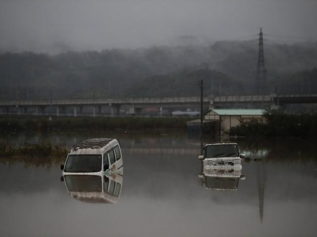 Two vehicles are submerged in floodwaters Monday, Oct. 14, 2019, in Hoyasu, Japan (AP Photo/Jae C. Hong)