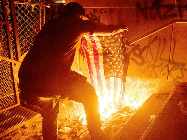 Protester burns an American flag outside the US Courthouse on July 20, 2020, in Portland, Ore. (AP Photo/Noah Berger)