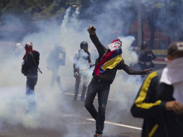 Opositores a Maduro se enfrentan con la policía en Caracas, Venezuela. Foto: AP / Ariana Cubillos