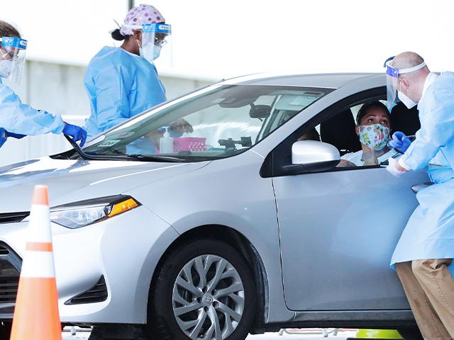 Healthcare workers gather information before conducting an antigen test, Aug. 5, 2020, at a COVID-19 testing site in Miami Gardens, FL. Antigen testing reveals whether a person is currently infected with COVID-19. (AP Photo/Wilfredo Lee)