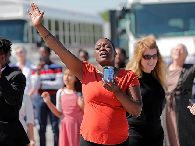 Members of the Life Tabernacle Church sing spiritual songs and hold their hands in the air as they wait for pastor Tony Spell to leave the East Baton Rouge Parish jail in Baton Rouge, La., April 21, 2020. (AP Photo/Gerald Herbert)