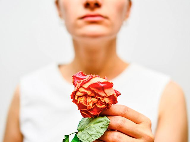 Woman holding dead rose
