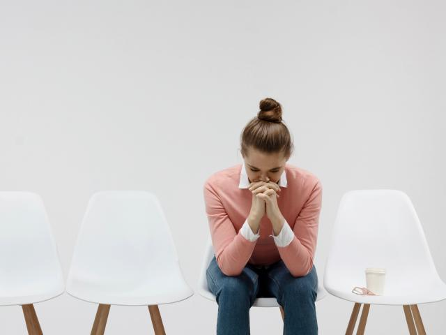 woman in pink sweater waiting in white room with white chairs