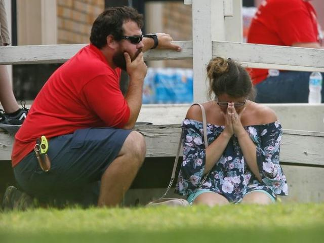 A woman prays in the grass outside the Alamo Gym where parents wait to reunite with their kids following a shooting at Santa Fe High School Friday, May 18, 2018, in Santa Fe, Texas.