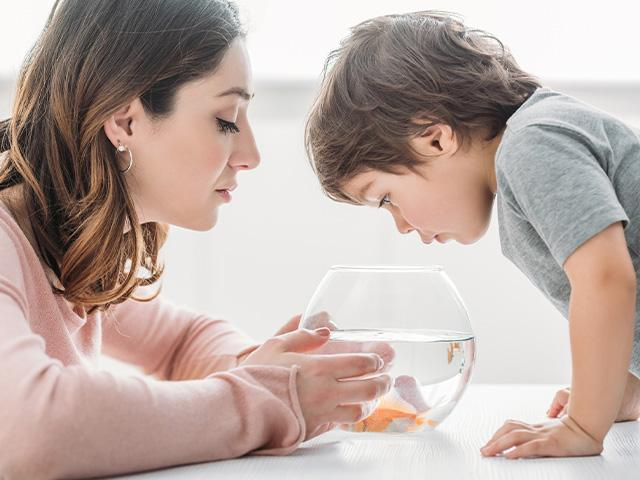mother and son looking in a fishbowl at a goldfish