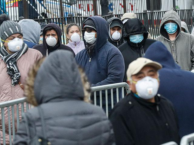 Patients wear personal protective equipment while maintaining social distancing as they wait in line for a COVID-19 test at Elmhurst Hospital Center, March 25, 2020, in New York (AP Photo/John Minchillo)