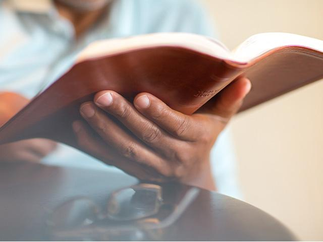 close up of an open Bible in a man