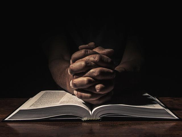 praying hands on top of an open Bible