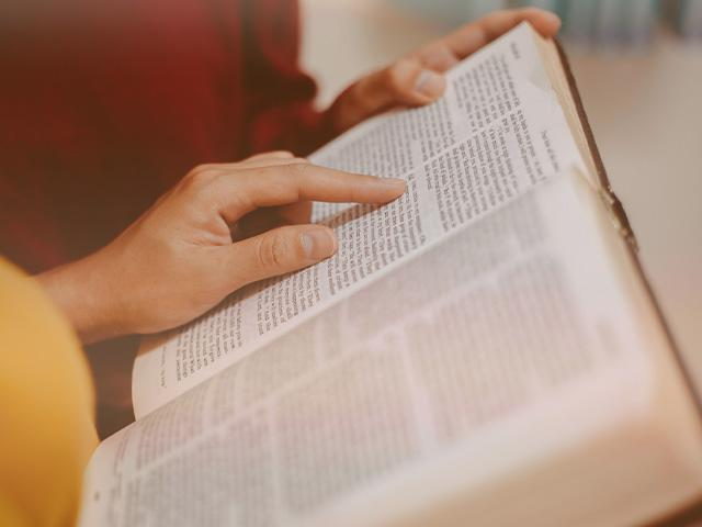 two people with open Bible reading Scripture together