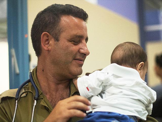 Operation Good Neighbor. Commander comforts a Syrian baby. Photo, IDF
