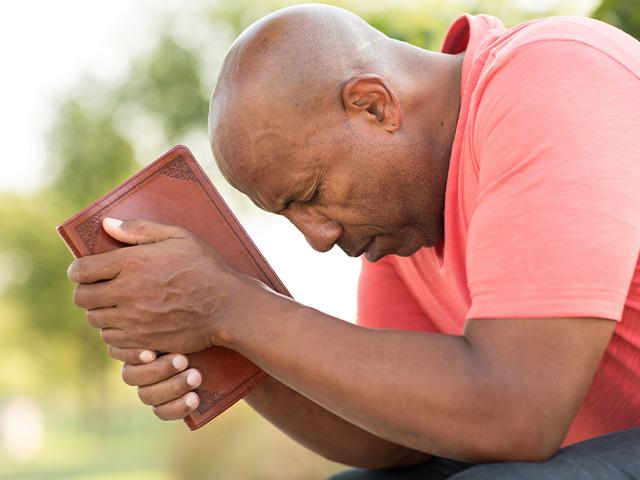 man praying outside with a Bible in his hands