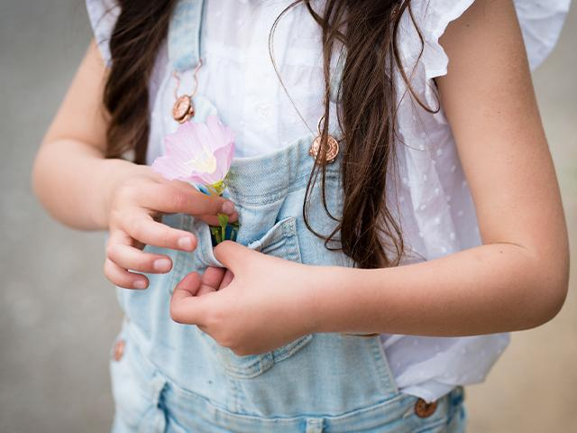 little girl putting a flower in the pocket of her overalls