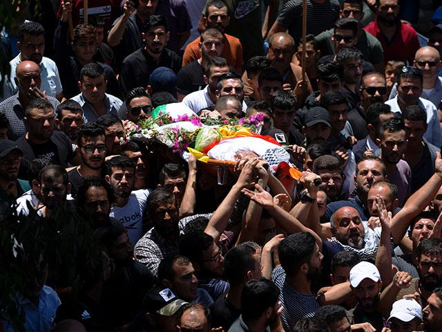 Palestinians carry the body of Mohammed al-Alami, 12, during his funeral in the village of Beit Ummar, Thursday, July 29, 2021. (AP Photo/Majdi Mohammed)