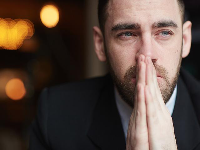 man praying with eyes open and distracted in thought