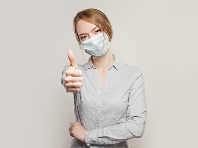 woman wearing a face mask with thumbs up gesture