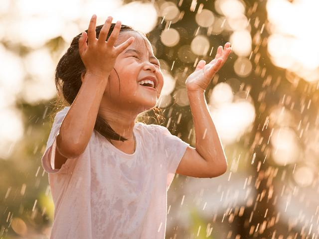 little Asian girl smiling while getting wet in the rain