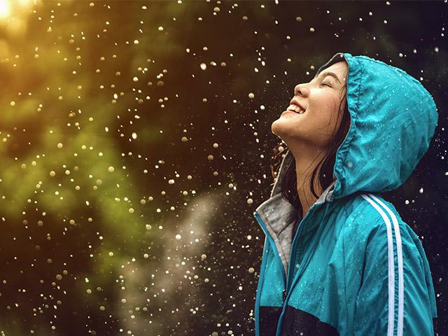 young woman wearing raincoat and smiling in the rain