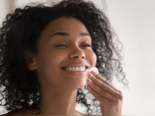 woman removing makeup with a cotton ball