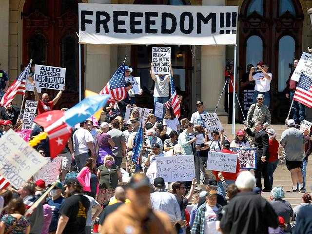 People protest at the State Capitol during a rally in Lansing, Mich., May 20, 2020. Barbers and hair stylists are protesting the state's stay-at-home orders as small businesses are eager to reopen (AP Photo/Paul Sancya)