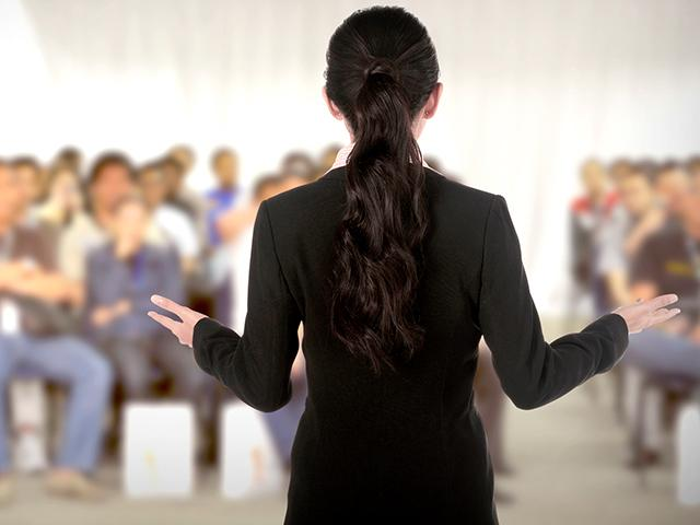 female speaker to crowd at a conference