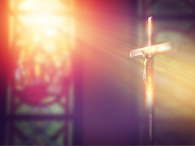 sun ray shining through church window to Jesus on the cross