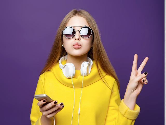 teen girl wearing earphones and giving the peace sign