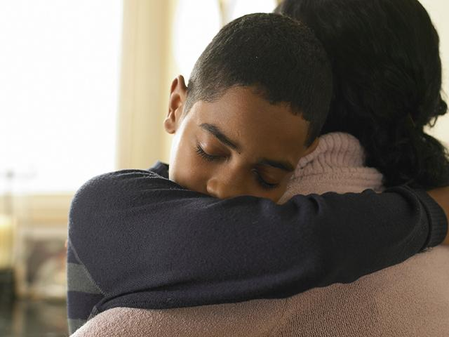 teen boy hugging his mother