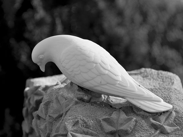 a white dove sculptured on top of a tombstone