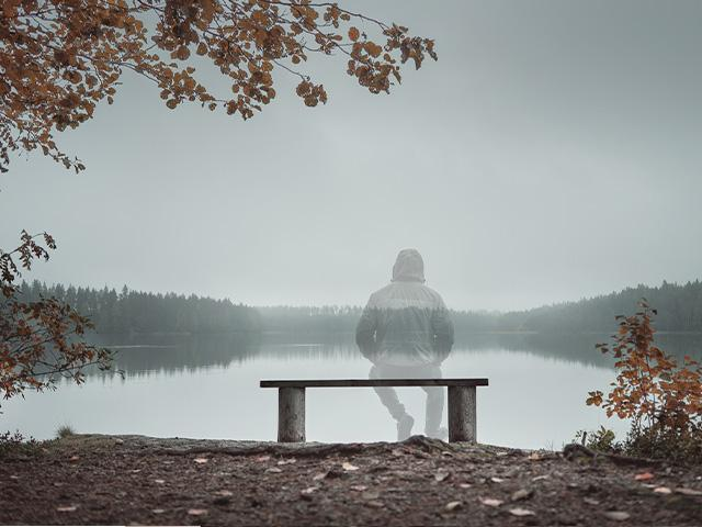 transparent man sitting on a bench by a lake