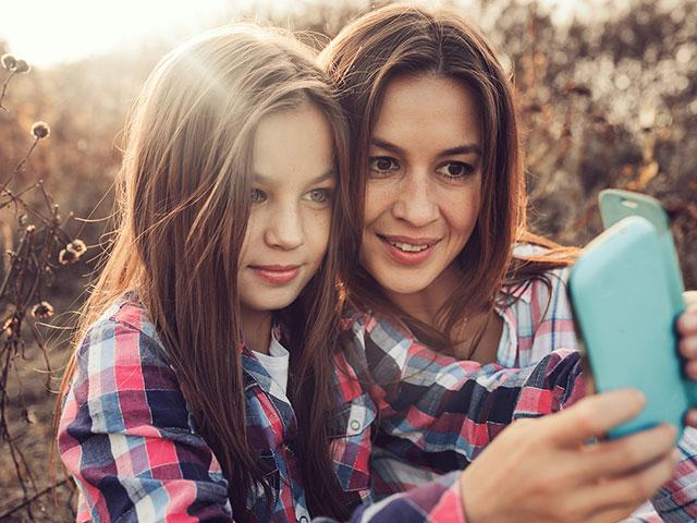 Tween girl with mom on cell phone