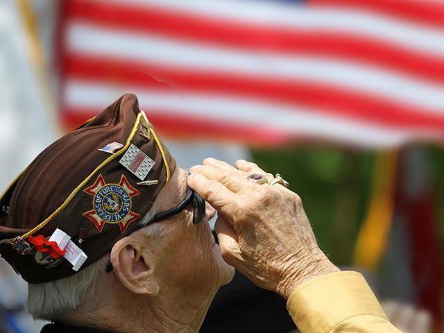 Veteran saluting American flag