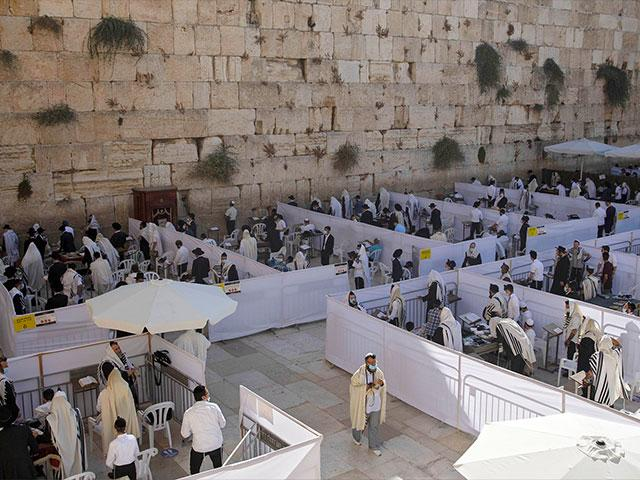 Ultra-Orthodox Jewish men pray in divided sections which allow a maximum of twenty worshipers, at the Western Wall. (AP Photo/Sebastian Scheiner)