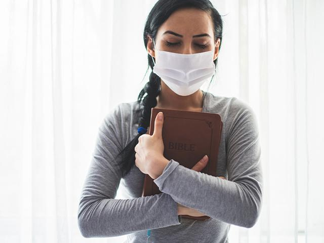 woman hugging her Bible and wearing a face mask during covid19 pandemic