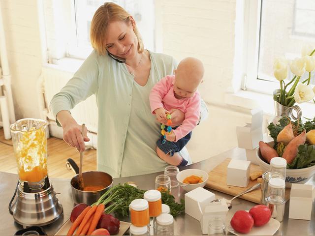 woman talking on her phone with a baby on her hip and cooking on the stove