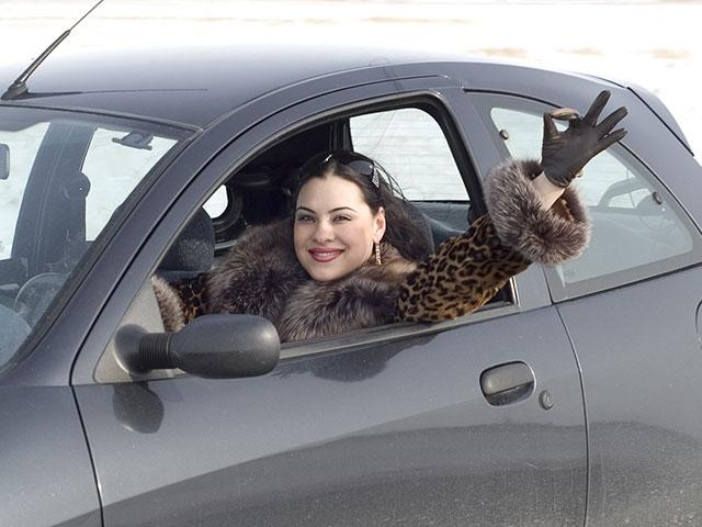 woman driving and giving okay hand signal