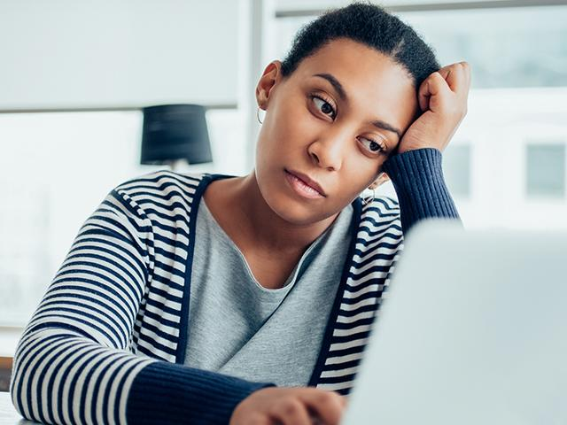 exhausted woman sitting with her laptop