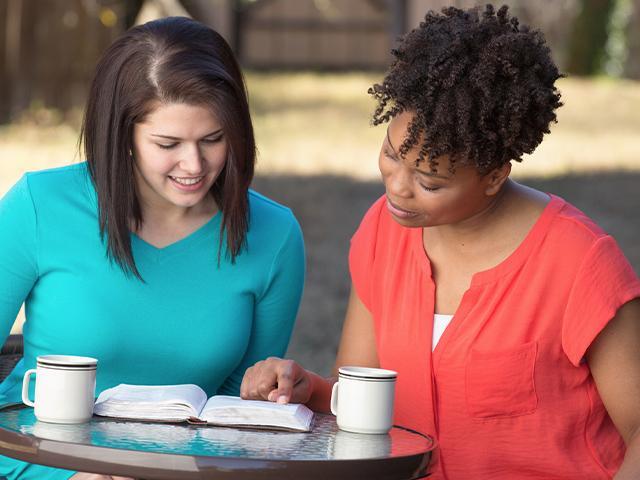 women with open Bible having a conversation