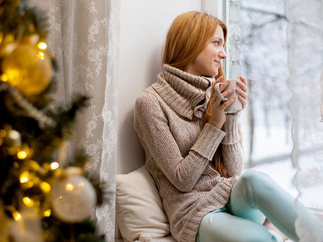 Young woman drinking coffee at Christmas