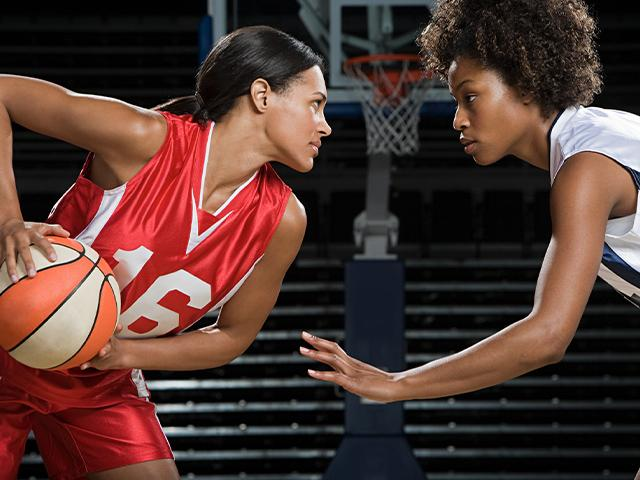 two young women playing basketball in uniforms