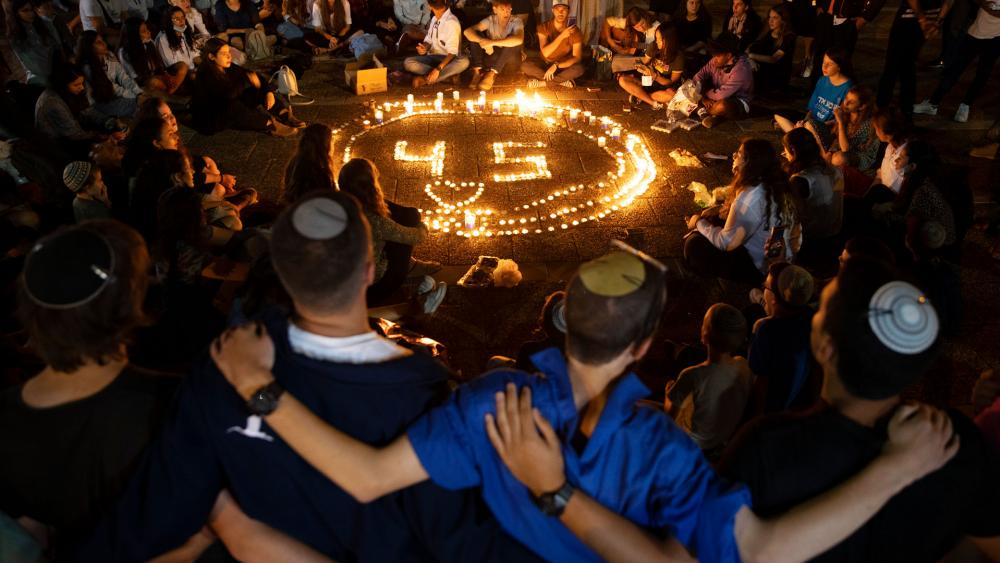 People gather around candles during a vigil in memory of the 45 ultra-Orthodox Jews killed in a stampede at a religious festival in northern Israel on Friday, in Tel Aviv, Israel, Sunday, May 2, 2021. (AP Photo/Oded Balilty)