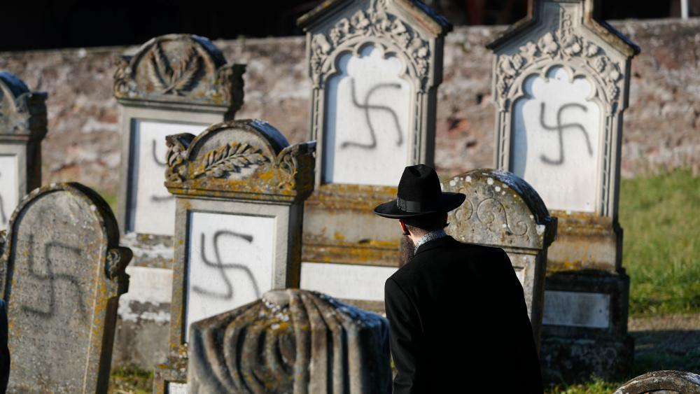 In this Dec. 4, 2019 file photo, Strasbourg chief Rabbi Harold Abraham Weill looks at vandalized tombs in the Jewish cemetery of Westhoffen in eastern France.  (AP Photo/Jean-Francois Badias, File)
