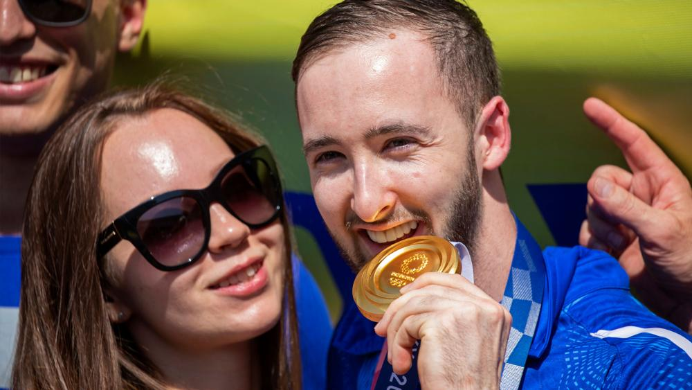 Artem Dolgopyat, Israeli artistic gymnastics men's gold medalist of Tokyo 2020, stands with his partner Maria Masha Sakovichas, while holding his medal. (AP Photo/Ariel Schalit)
