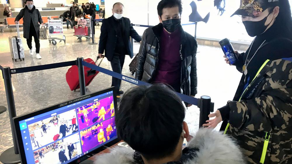 Travelers pass through a health screening checkpoint at Wuhan Tianhe International Airport in Wuhan in southern China's Hubei province, Tuesday, Jan. 21, 2020. (AP Photo/Emily Wang)