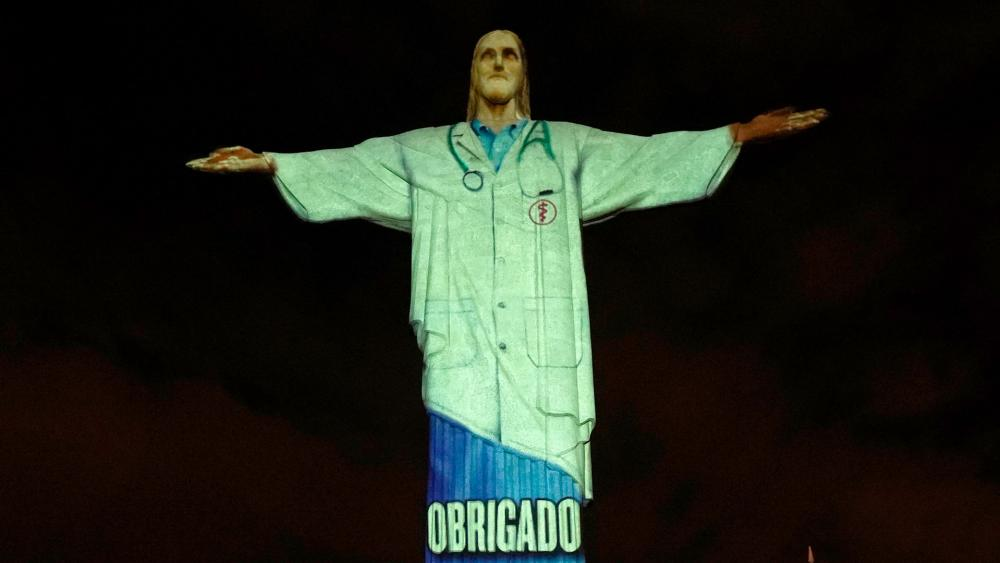 "Rio's Christ the Redeemer statue is lit up like a doctor and with the word ""Thanks"" projected in Portuguese, during an Easter service, in the midst of the new coronavirus pandemic, Rio de Janeiro, Brazil, April 12, 2020. (AP Photo/Silvia Izquierdo)"