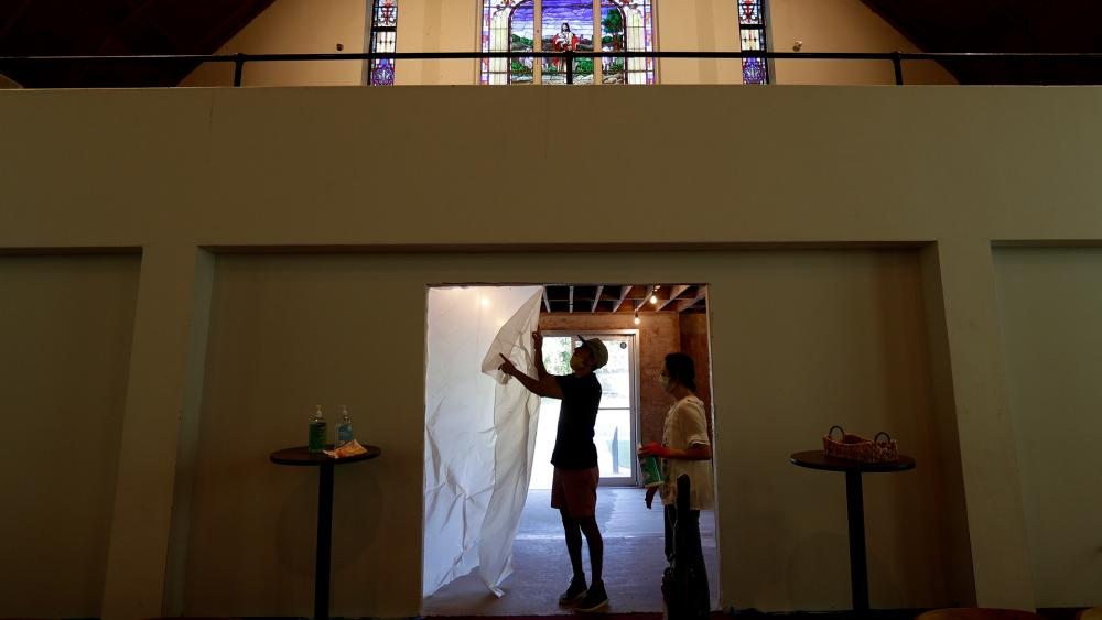 Alamo Heights Baptist Church pastor Bobby Contreras and his wife Hannah work to clean, sanitize and prepare the church for services in San Antonio, May 6, 2020. (AP Photo/Eric Gay)